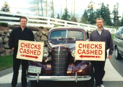 Founders Dennis and Dave Bassford standing with signs reading 'checks cashed' with arrows pointing to a 1983 Chevy.