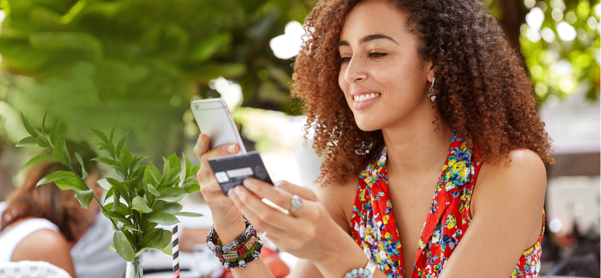 Woman with curly hair smiling as she checks her prepaid card balance on her cell phone. Get a Prepaid card from Moneytree.