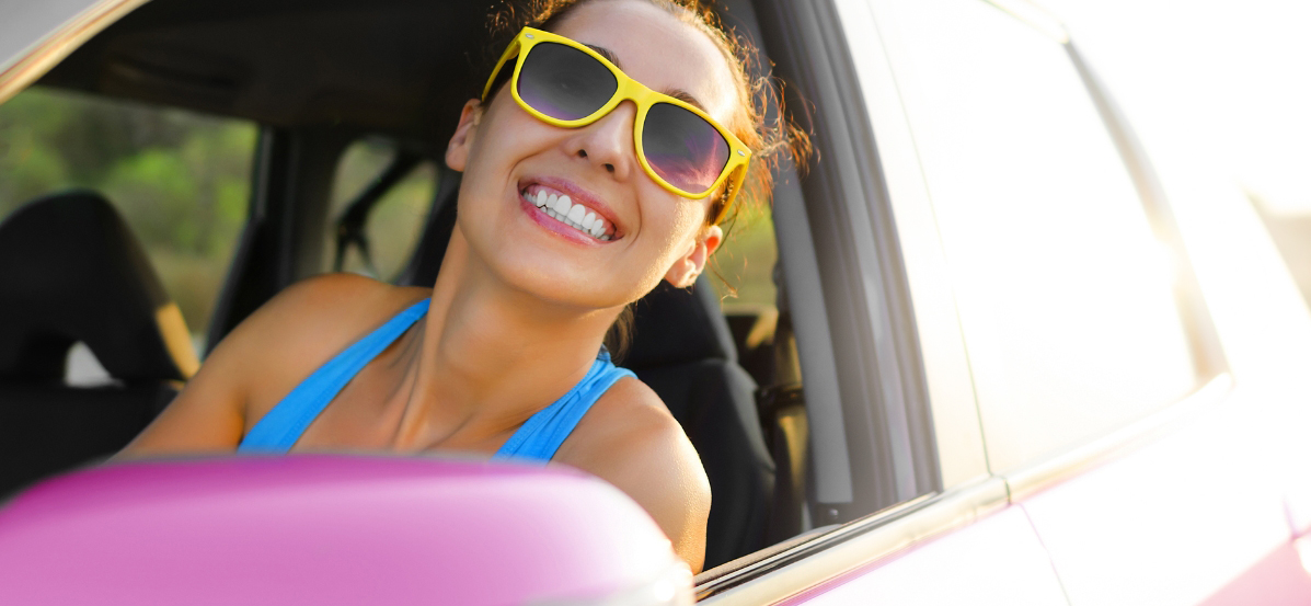 Woman with yellow sunglasses smiling from a car window