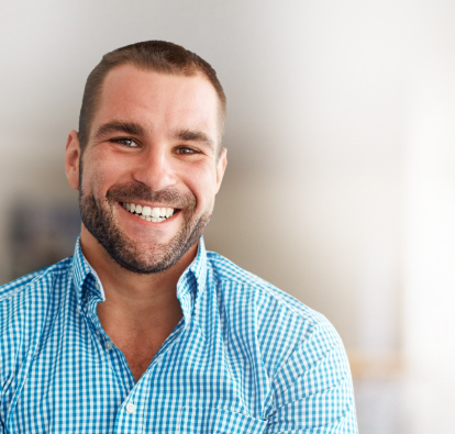 Man with blue button up shirt smiling.