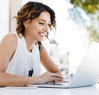 Smiling woman sitting at a table and typing on a laptop.