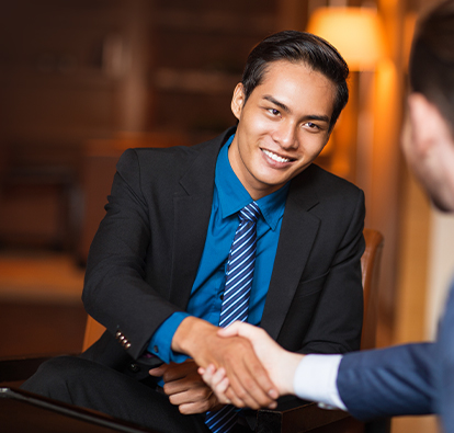 Man smiling in a suit, shaking hands with another man.