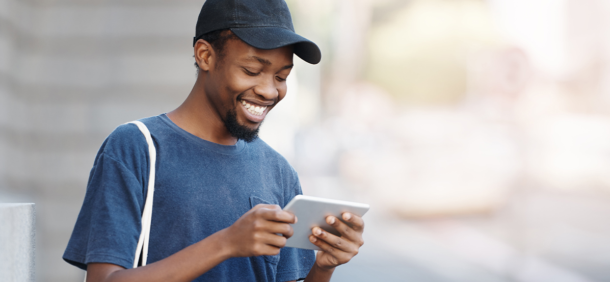Man with baseball cap, smiling and looking at a mobile device.
